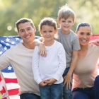 Happy family holding american flag in the park on a sunny day